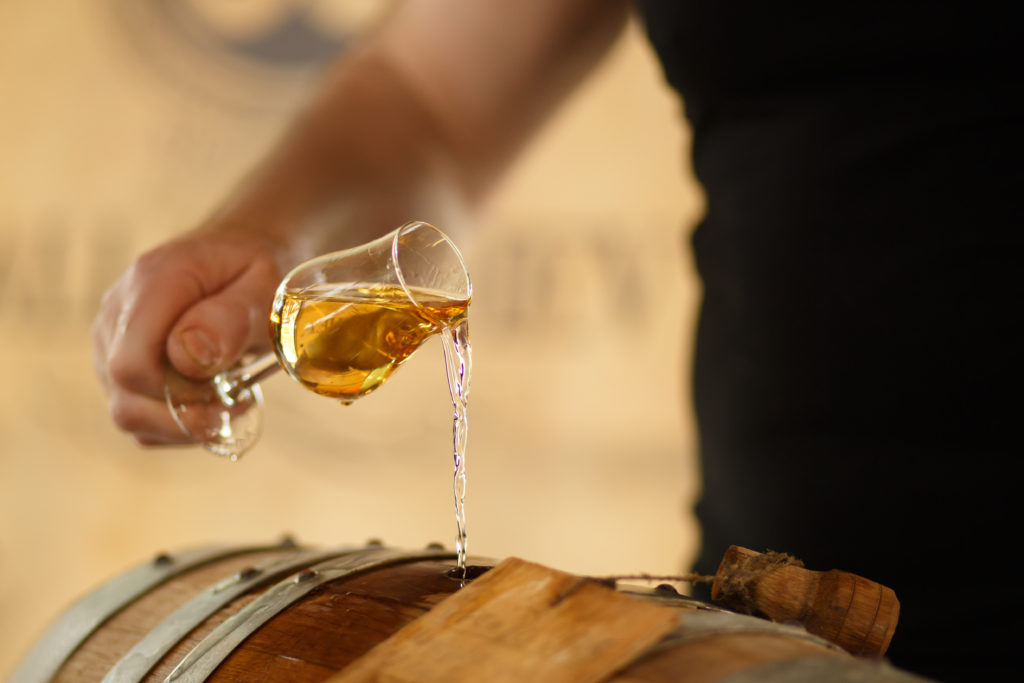 pour whiskey in barrels